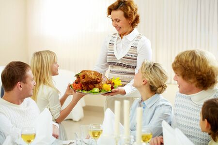 Portrait of big family sitting at festive table and looking at aged female with dish of delicious turkey Stock Photo - 8227293