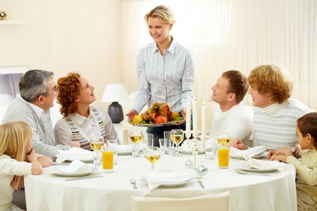 Portrait of big family sitting at festive table and looking at pretty woman with dish of roasted turkey photo