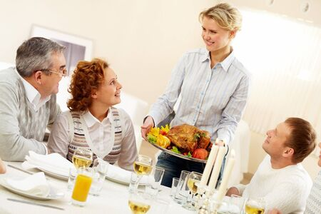 Portrait of senior couple and happy man pretty woman with roasted turkey going to put it on festive table photo