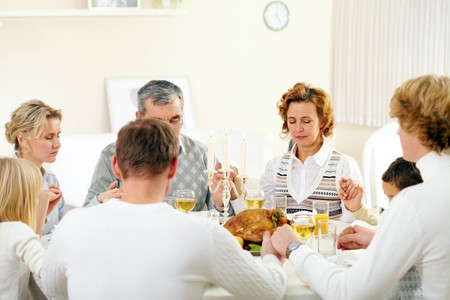 religious event: Portrait of big family sitting at festive table and holding each other by hands while praying Stock Photo