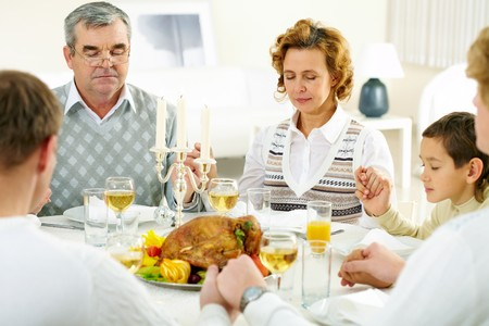 Portrait of big family sitting at festive table and praying before dinner photo