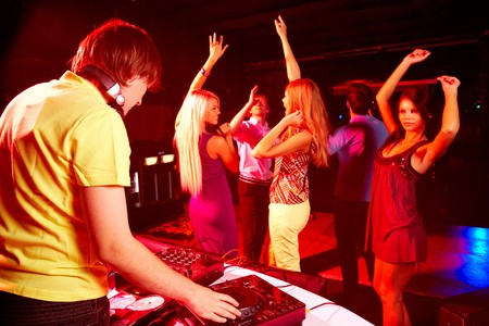 Smart deejay spinning turntables with dancing teens on background photo