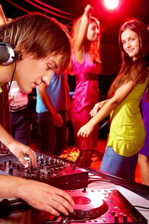 Smart deejay adjusting technics with dancing girls on background photo