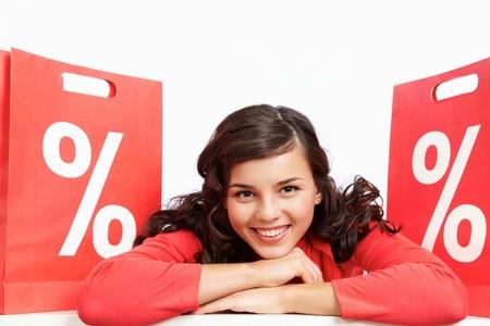割引: 赤の紙袋の間横になっていると、カメラを見て幸せな買い物客の肖像画 写真素材