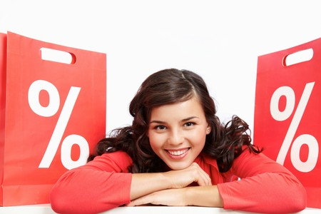 percentage sign: Portrait of happy shopper lying between red paper bags and looking at camera Stock Photo