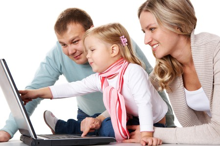 computer user: Friendly family looking at laptop monitor in studio