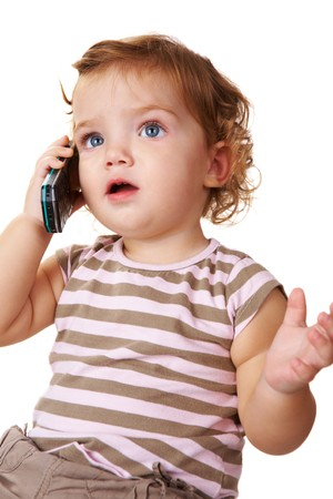 Portrait of cute toddler speaking by cellular phone photo