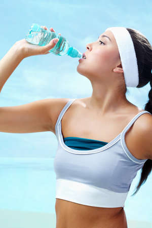 Portrait of lovely girl holding bottle of water in hand and drinking photo