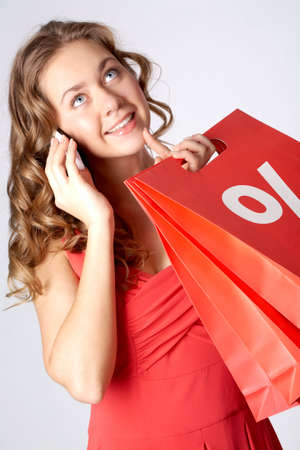 Portrait of a girl holding paper bags with discount symbol, calling on the cellphone and smiling  Stock Photo - 8227358