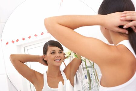 Image of pretty female looking in mirror in the morning photo