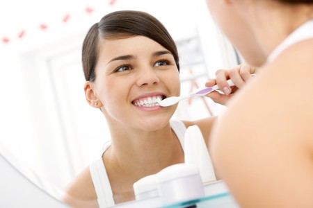 Image of pretty female brudhing her teeth in front of mirror in the morning photo