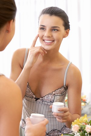 woman face cream: Portrait of pretty female applying cream onto her face and smiling