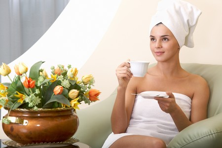 girl with towel: Portrait of clean girl with towel on head drinking tea in beauty salon Stock Photo