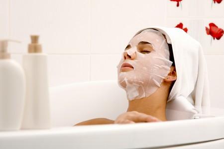 sensitive skin: Image of serene woman with facial mask enjoying bath in spa salon