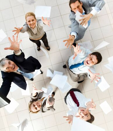 businessteam: Above view of several successful partners throwing papers in joy  Stock Photo