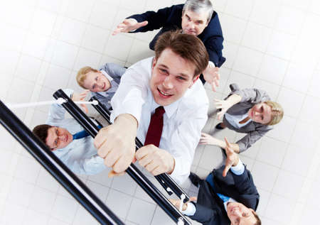 corporate ladder: Above view of businessman ascending the ladder with his crew beneath Stock Photo