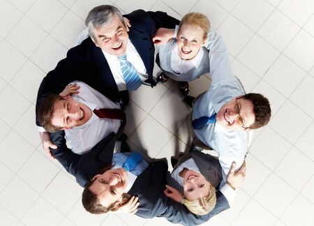 employees group: Above view of several happy business partners looking at camera while embracing each other Stock Photo