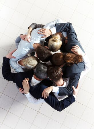 Above view of several business partners embracing each other while making circle Stock Photo - 8227657