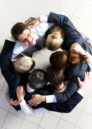 Above view of several business partners embracing each other while making circle with one of them looking at camera Stock Photo - 8227696