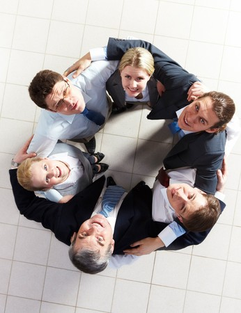 Above view of several business partners looking upwards at camera while embracing each other Stock Photo - 8227612