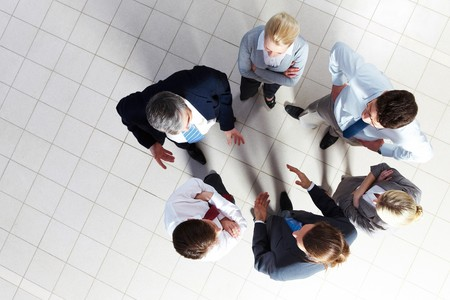 people interacting: Above angle of several smart associates talking to each other at meeting Stock Photo