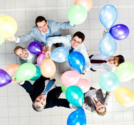 actitud positiva: Por encima de la vista de varios socios de �xito con globos de colores mirando la c�mara  Foto de archivo