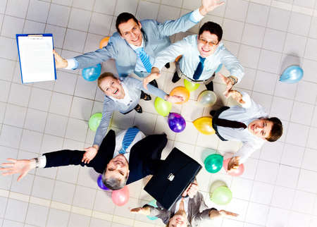 Above view of joyful business people looking at camera with balloons on the floor  photo