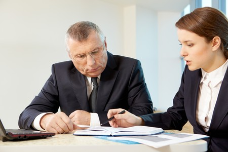Boss and secretary planning work in office photo