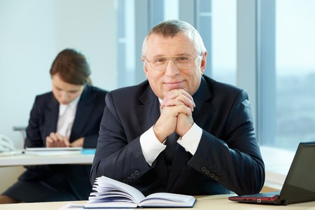 Senior business leader looking at camera at workplace photo