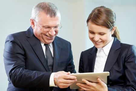 Boss and secretary looking at modern gadget with smiles during discussion photo