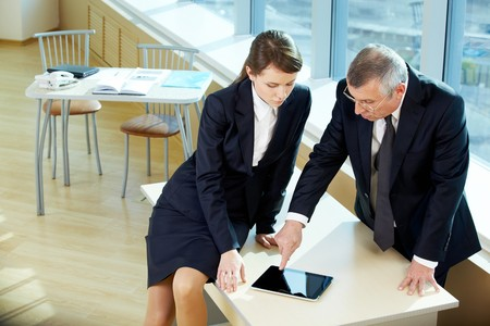Boss pointing at digital screen during explanation of something to secretary photo