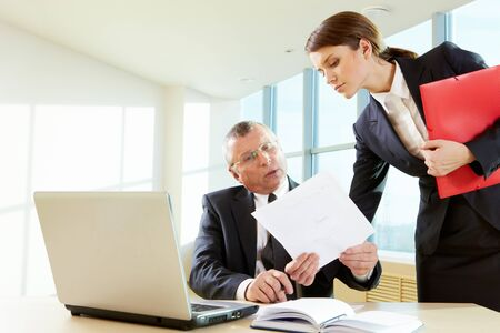 employer: Pretty female showing document to her boss in the office