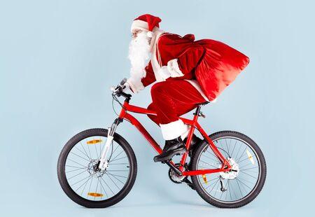 riding bike: Foto di Babbo Natale felice con rosso sacca bici