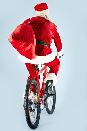 newyear: Rear view of Santa Claus with red sack riding bike Stock Photo