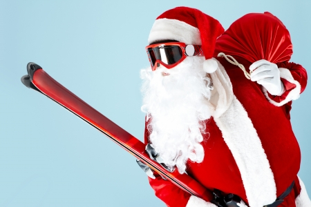 xmass: Photo of happy Santa Claus with skis looking through goggles Stock Photo