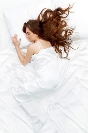 durmiendo: Por encima de la vista de la joven y bella mujer durmiendo en la cama cubierta con hoja de seda blanca