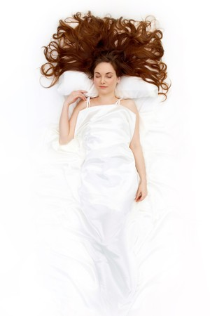 white pillow: Above view of resting female under linen sheet with her long hair spread on pillow