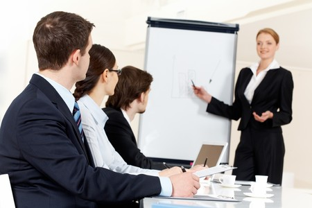 Photo of serious business people listening to female manager pointing at whiteboard while presenting new project Stock Photo - 8228214