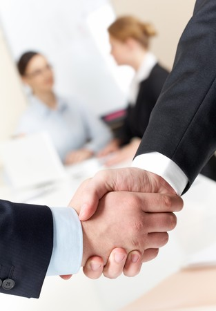 great deal: Photo of handshake of businessmen on background of communicating co-workers Stock Photo