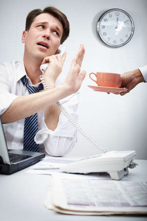 Portrait of busy chief calling by phone and refusing from cup of coffee held by his secretary  photo
