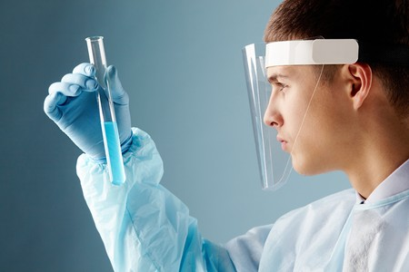 Serious clinician looking at flask with blue liquid through transparent safe mask Stock Photo - 8228517