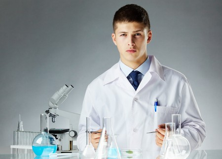 cientificos: Cl�nico grave con herramientas de acero mirando la c�mara en laboratorio