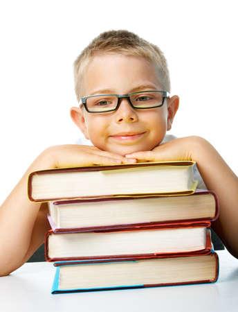 diligente: Cara de colegial diligente con la cabeza en la pila de libros sobre fondo blanco