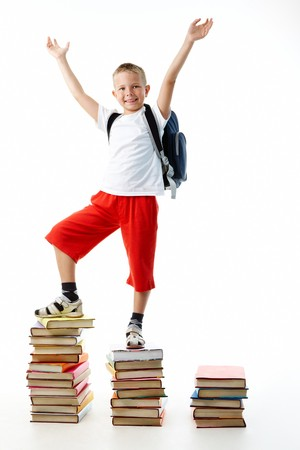 diligent: Diligent preschooler standing on the top of book stairs with his arms raised