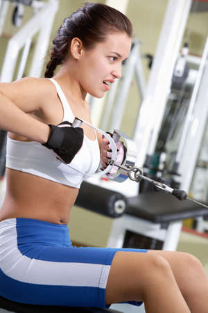 Photo of active girl pumping muscles on special equipment photo