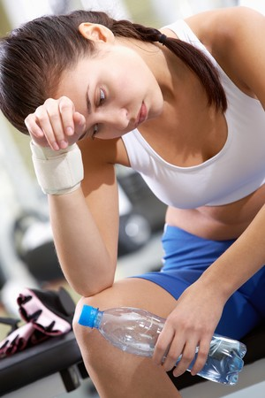 Portrait of tired brunette with bottle of water in hand having rest after workout photo