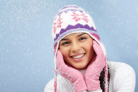Face of pretty woman in pink gloves and knitted winter cap looking at camera with smile photo