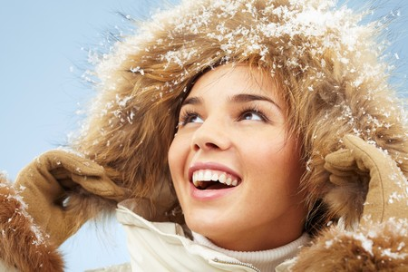 Happy woman with furry hood on head in good mood photo