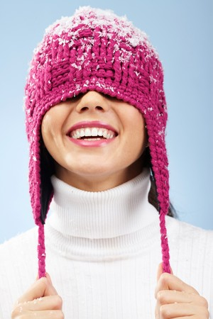 fresh snow: Portrait of playful woman in knitted winter cap smiling