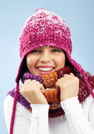 Face of pretty woman in knitted winter cap and scarf looking at camera with smile photo